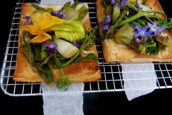 Spring vegetable and flower savory tart with goat cheese on oven rack