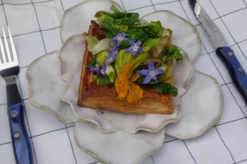 Spring vegetable and flower savory tart with goat cheese on plate