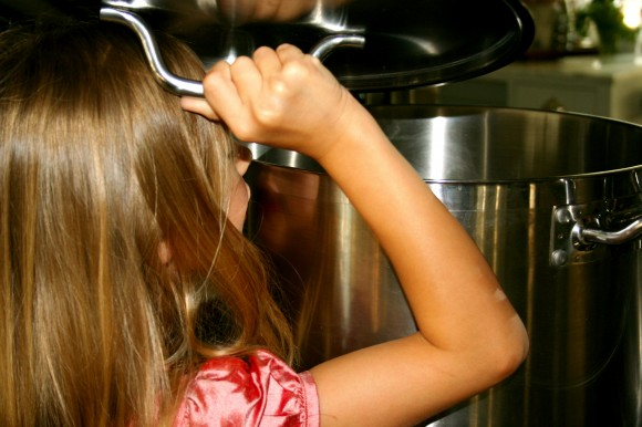 Child looking into kitchen pot