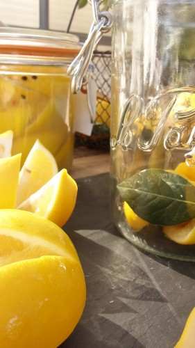 quartered and salted lemons  with lemon juice in glass jar