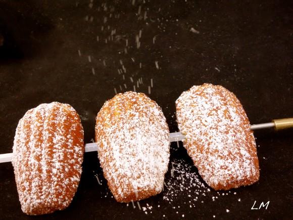dusting powdered sugar  on three Madeleine's