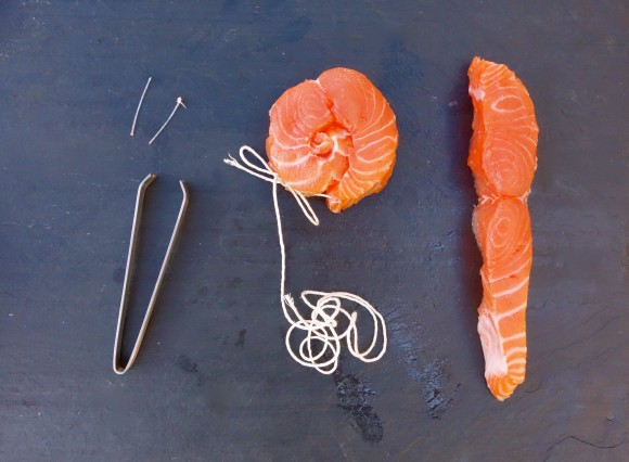 salmon filets with string and tongs one filet has been rolled and tied with string