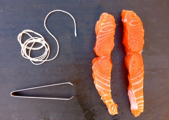 salmon filets with string and tongs